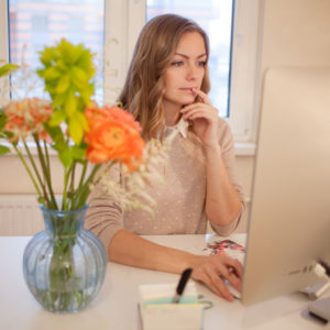 Young businesswoman sitting at desk and working. Beautiful woman and her workplace